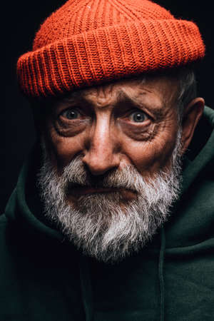 Face portrait of elderly fishman wearing orange hat and green warm hoodie, having white beard and wrinkled weathered face, looking at camera with hopeless gloomy expression