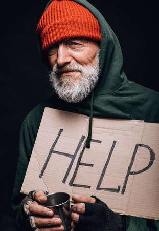 Jobless poor old aged male beggar in orange warm hat looking at camera with a handwritten sign for help holding a cup for coins in hands. Isolated studio shot over black background.
