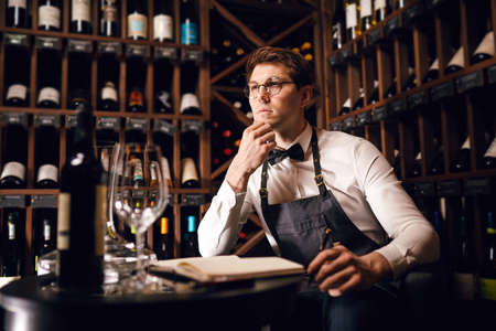 Handsome and young smiling brown haired sommelier with a bottle of winer on the background o dark wine house with shelves of bottles with alcohol