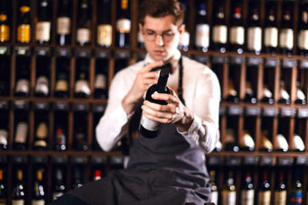 Young caucasian cavist dressed in white shirt and bowtie working in big wine shop presenting a bottle of red wine to customer