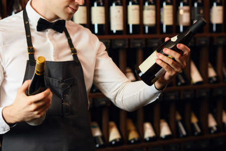 Elegant wine seller holding a bottle of wine and reading label in a wine store. Choosing wine according to its origin country and vintage. Standard-Bild