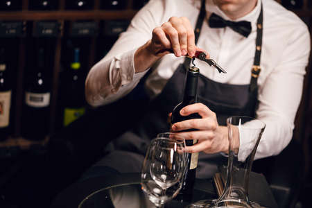 Elegant young sommelier with bow tie uncorking bottle of wine in wine boutique. Wine tasting social event.