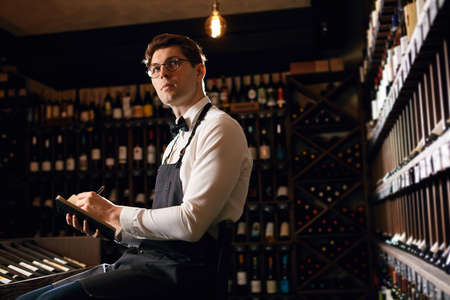 Professional male Sommelier dressed in bowtie and apron writes at notepad, putting down information on wine bottles in wine house