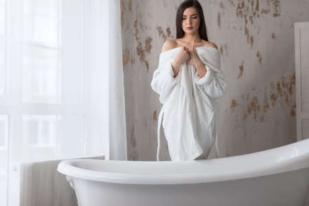 Brunette spa caucasian girl with white young skin, wearing white bathing robe, preparing to bath, looking down, enjoying warm relaxing water over light background.