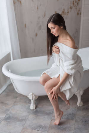 Young woman partially dressed in bathrobe, sits on the edge of bathtub and moisturising with cream her slim long barefoot legs after having bath