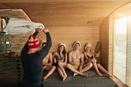 Group of caucasian young diverse people watching skillful bath attendent in black wear and red hat, accelerates steam with a towel, heats the air evenly in wooden steam-room