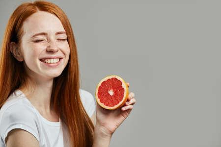 laughing awesome charming girl with closed eyes is holding a half of grapefruit. yummy fruit, tasty vitamine