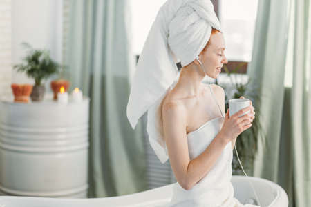 Optimistic glad caucasian female tourist in bath wear with cheerful expression, using earphones and having herbal drink, preparing warm comforting bath after a day spent taking care of business