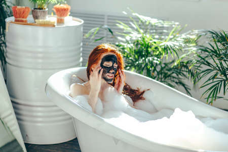Young beautiful red-haired girl making a clay face mask for beauty during spa treatments in the bathroom, enjoying sunlight and warm water in bathtub, resort and vacation concept, summer time Фото со стока