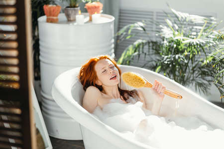 Emotional red-haired playful woman with bodybrush cheering and laughing as she singing song like a singer, having fun, while bathing at home. Self-expression and talent.