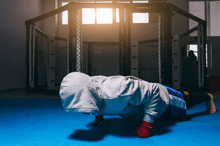 fitness, sport, exercising, training and lifestyle concept - young man in hooded sweatshirt doing push ups in boxing centre, warming up before workout.