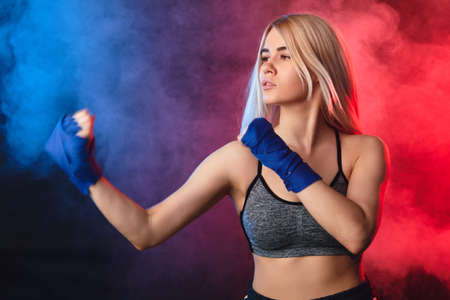 Attractive blonde woman fighter in boxing bandages posing in defense boxer stance isolated on dark smoky background in sport and fitness exercise workout.