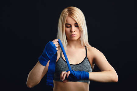 Young blonde female Muay Thai fighter wrapping his hands with blue elastic bandage preparing to workout on black background Stok Fotoğraf