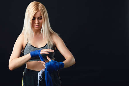 Young blonde female boxer wrapping his hands with blue elastic bandage preparing to workout on black background Stok Fotoğraf