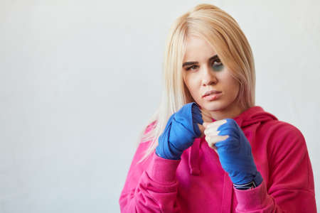 Female kick boxer with long blonde hair dressed in pink hoodie and boxing bandages looking at camera with bruise after match