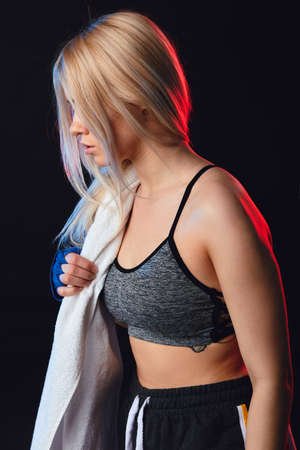 Sporty blonde female kickboxer fighter with white towel on neck after workout wearing kickboxing bandages, posing isolated over black background