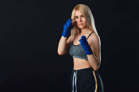 Beautiful determined blonde female boxer in blue handwraps getting prepared for big fight