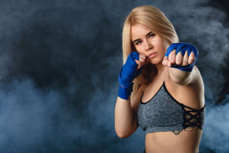 Young attractive kickboxing female fighter with blonde hair practicing punches. Kickboxer in blue bandages throwing punches for the fight. Dark smoky background Stok Fotoğraf
