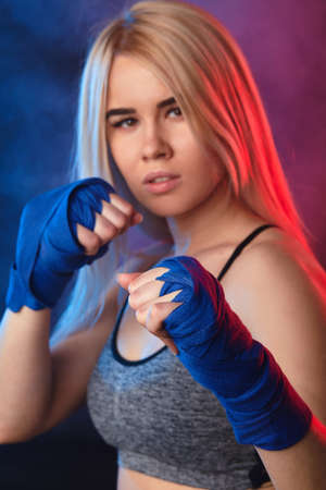 Close up face portrait of attractive blonde woman fighter in boxing bandages posing in defense boxer stance isolated on dark background in sport and fitness exercise workout.