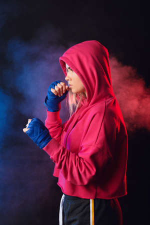 Blonde woman in pink hoodie and black shorts perfecting moves and kicks on Mixed Martial Arts classes at gym.