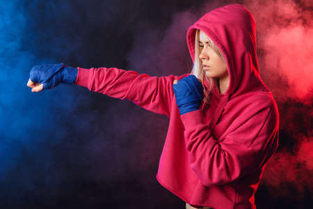 Young beautiful woman in pink sportswear with hood on, practicing punches while standing in dark gym with red and blue smoke. Sport and training concepts.