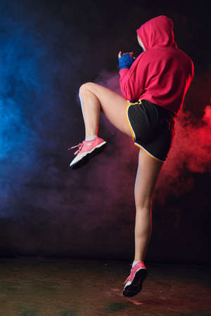 Young beautiful woman in pink sportswear with hood on, practicing punches while standing in dark gym with red and blue smoke. Sport and training concepts. Foto de archivo