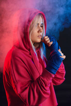 Female blonde boxer in pink hoodie prepares to punch at a boxing studio. Woman boxer in motion over black smoky background Stok Fotoğraf