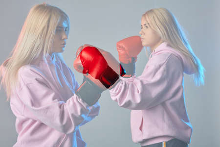 Two female boxers during a sparring in the boxing ring. Digital image one and the same woman in a pink hoodie, wearing red gloves, punching her copy during boxing exercise. Strength and motivation. Stok Fotoğraf