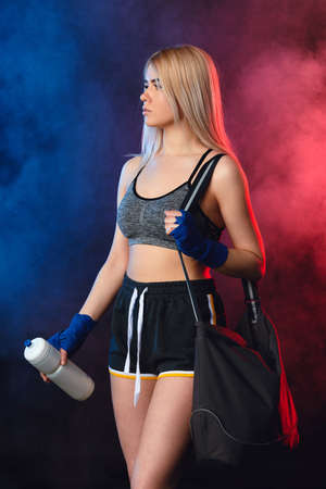 Attractive caucasian blonde woman in fashionable sportswear ready for sport on dark smoky background. Fit girl holds shaker in hands and carries sportbag on shoulder. Sports and healthy lifestyle Stok Fotoğraf