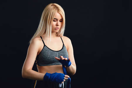 Young caucasian concentrated female athlete dressed in tank top wrapping his fists by blue elastic bandages to avoid serious problems with carpal joints while boxing