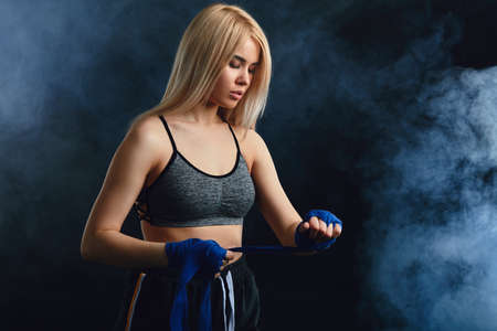 Blonde female athlete is exercising in defense and attacks on dark smoky background. Woman in tank-top and boxing bandages is having cardio boxing workout