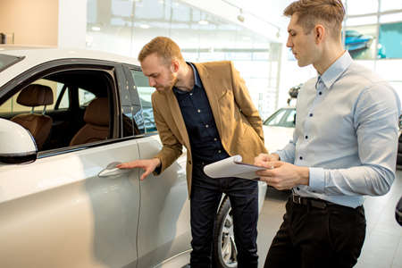 affable handsome caucasian consultant and client in dealership. young business man came to buy new automobile, happy future owner of representative car