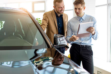 young caucasian cars salesman talk about advantages of car, recommend it to customer. business man choosing new representative business class auto in dealership