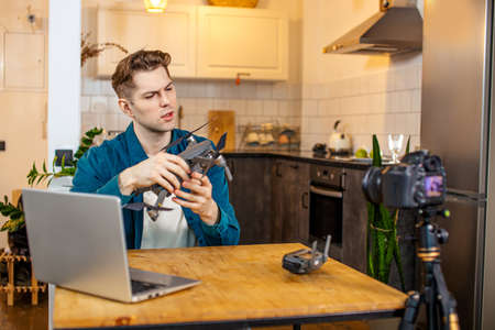 blogger man keen on engineering and modern smart technologies and devices, he show his new purchase to subscribers, sit in front of camera and talk about advantages and disadvantages Reklamní fotografie