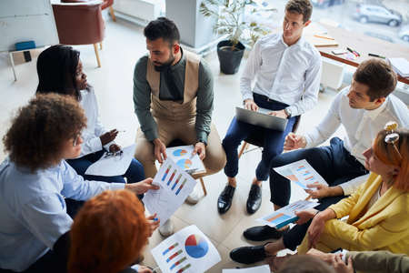 Modern and enthusiastic business people sit in circle discussing business ideas, steps for building business, using diagrams and papers. Stock Photo