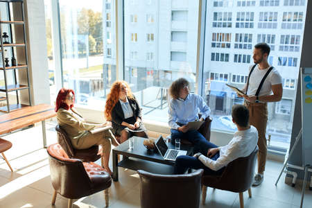 A secretary, personal assistant, an accountant getting daily tasks from the manager, their boss is listening to the group. Company employees meeting at the office. 5 caucasian people of both genders.