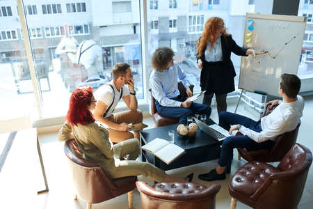A female business consultant reading a lecture for a group of young professionals. Open space office, a businesswoman and 3 businessmen are introduced to the research about corporate governance. Stock fotó
