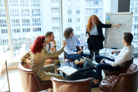 A female boss debating with employees during efficiency charts presentation. A group of businessmen of both genders having a work conference at a specious and bright office with panoramic windows. Foto de archivo