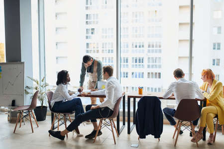 Executives having friendly discussion during break, business ideas, building business strategy while sititng on table together . office background