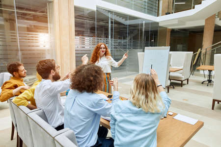 Charming attractive lady stands in front of curious team, points at white paper desk, holds pencil, looks aside with gentle smile in modern office, left side shot