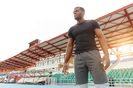Young serious strong sporty man in stylish sportswear standing on stadium running track looking aside. close up low view. copy space.motivation