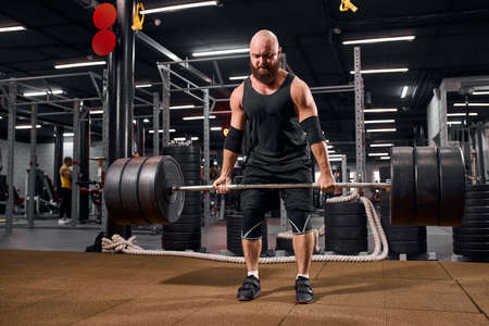 Strong sporty bodybuilder dressed in black sportswear, keeping heavy metal barbell in hands, looking away, showing power, doing lifting exercise, energy fitness motivation concept