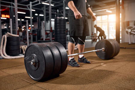 Heavy beautiful barbell on floor of gym, male legs standing near bar, bodybuilder practicing for training, active people, professional sport concept