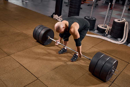 Brutal young male athlete bending in front of heavy iron barbell in gym hall, preparing for workout, practicing in studio active people lifestyle, side shot