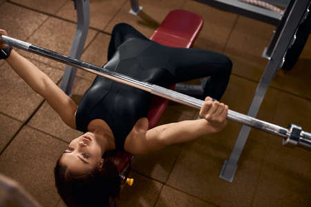 Beautiful powerlifter with strong arms lifting weights in sports hall, looking away, holding iron bar, exercising with heavy barbell, training hard for competition of weightlifting, high angle shot