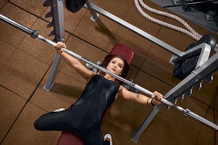 Indoor shot of beautiful female athlete in stylish sports clothes enjoying powerlifting training, holding barbell, lying on bench, looking away with concentrative look, energy motivation concept