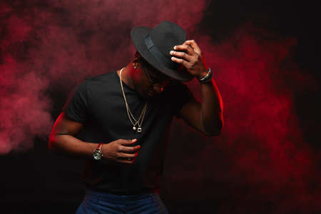 Portrait of handsome young african DJ or jazz musician in creative hat in black t-shirt on dark background