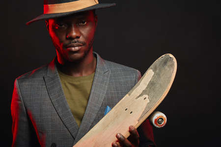 Formally dressed African man standing in studio with a longboard on dark background. Businessman standing against a wall indoors holding a long skateboard.