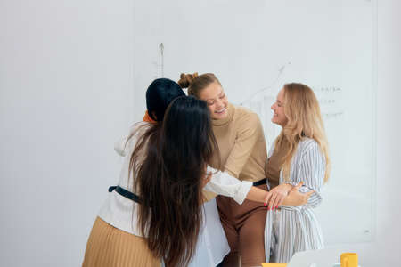 Young beautiful caucasian and african ladies wearing casual clothes hug each other celebrating their win in project. White modern office background
