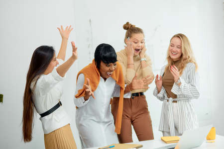 Surprised women in casual wear in office together, in shock with opened mouth. Celebrate their win in business project, good job of diverse female